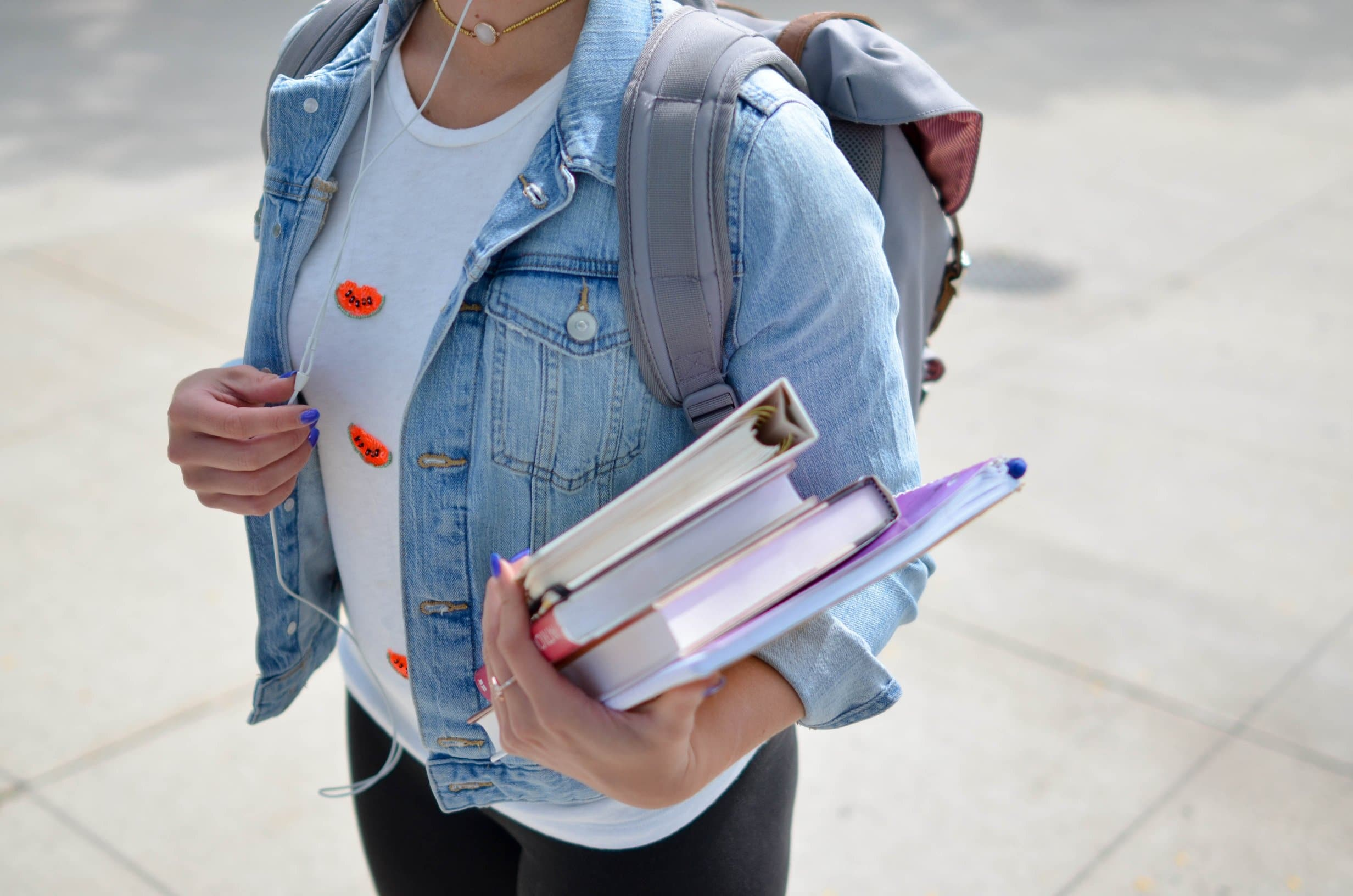female student at a campus holding books