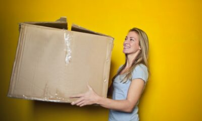 woman-in-grey-shirt-holding-brown-cardboard-box