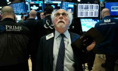 A trader on the floor of the New York Stock Exchange reacts Monday to plunging stock prices that forced a 15-minute halt to trading.