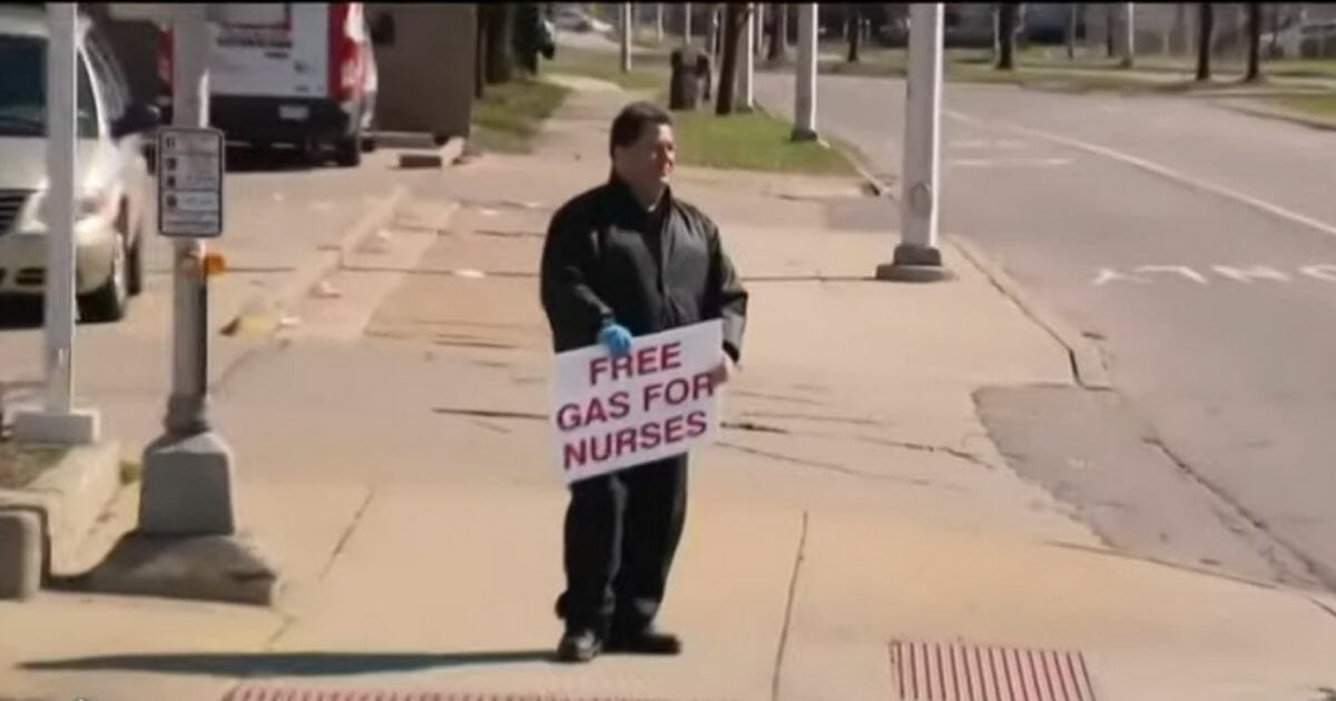Man stands at the corner with a sign using $900 from his own wallet to buy petrol for nurses.
