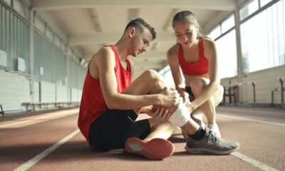 woman-helping-sportsman-with-injury