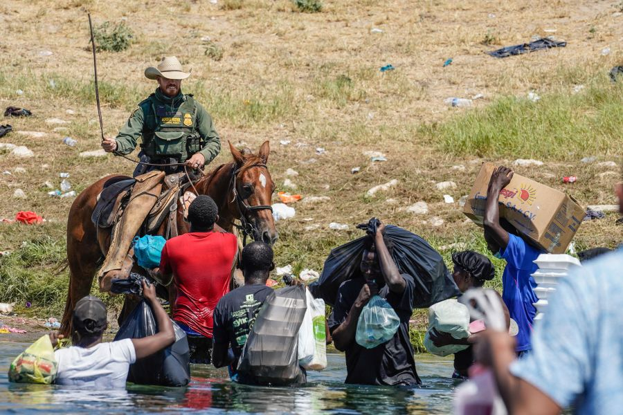 """Some photographs of U.S. Border Patrol agents on horseback facing off Haitian migrants near the Rio Grande in Del Rio, Texas, are causing outrage. Even the White House is calling them """"horrific."""" Many who've seen the images on social media say they appear to show the agents in cowboy hats whipping migrants of color. But the photographer who took the now-viral stills last Sunday says that's not the case."""