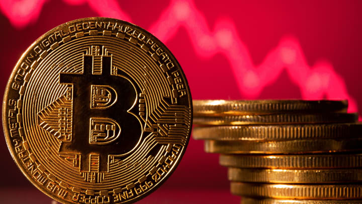 Picture of a gold bitcoin with a stack of gold bitcoins next to it and a red downward trend line behind it